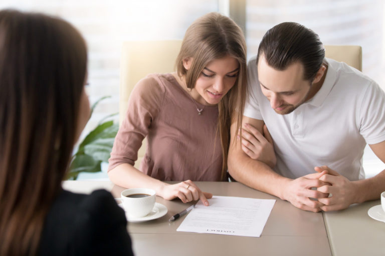 man and woman signing prenuptial agreement